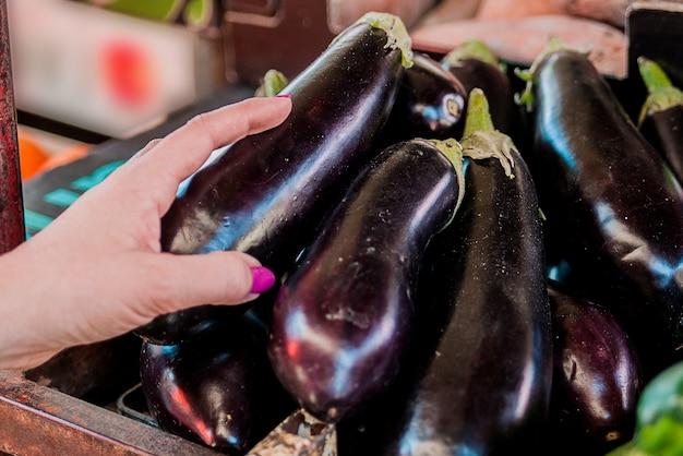 Hand op verse aubergines - aubergines, close-up. vrouwelijke keuze. vrolijke jonge vrouwelijke klant die verse aubergine op fruitmarkt kiest Gratis Foto