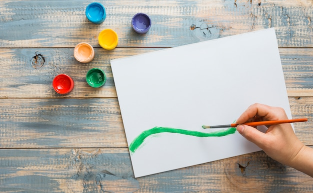 Hand puttend uit wit papier met groene aquarel penseelstreek Gratis Foto