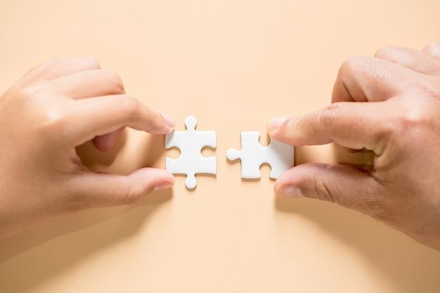 Hand puzzelstukken op tafel verbinden Gratis Foto