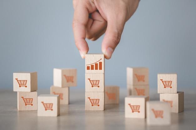 Hand schikken houtblok stapelen met pictogram grafiek en winkelwagentje symbool opwaartse richting, Premium Foto