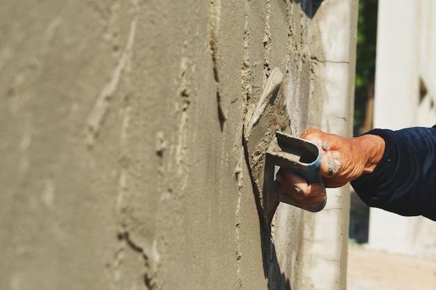 Hand van arbeider het pleisteren cement op muur Premium Foto