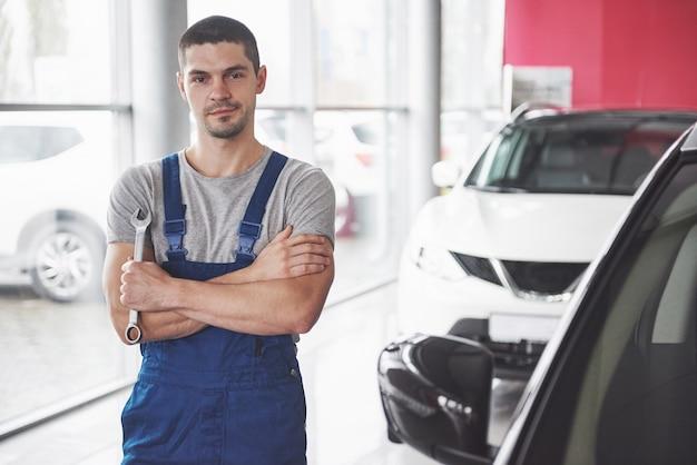 Hand van automonteur met moersleutel. auto reparatie garage. Gratis Foto
