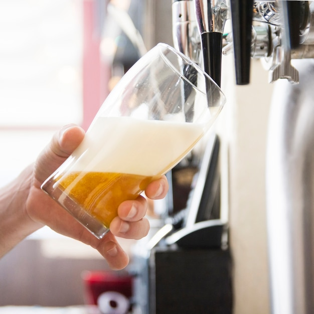 Hand van barman die een groot lagerbierbier in kraan gieten Gratis Foto