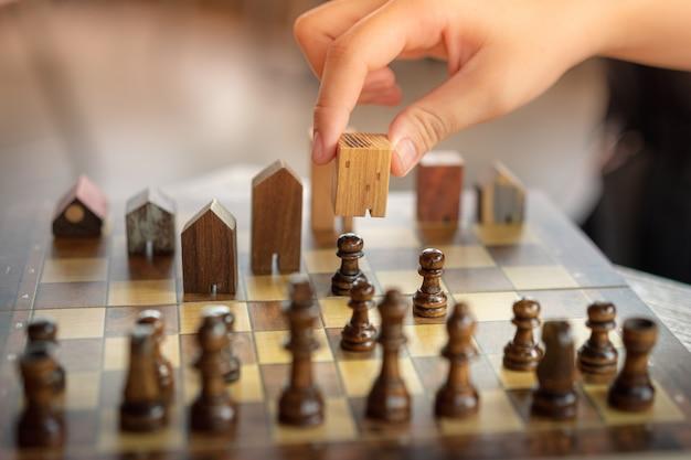 Hand van bedrijfsmensen bewegend schaak aan de bouw en huismodellen in schaakspel Premium Foto