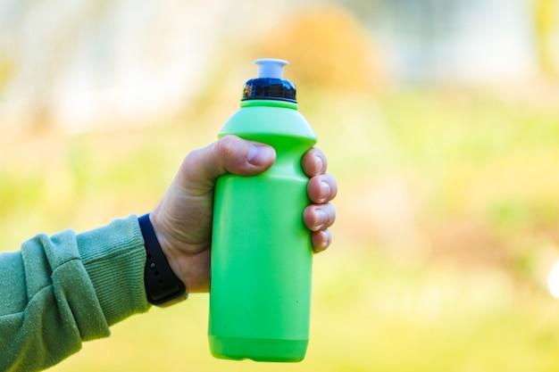 Hand van de jonge mens die de groene fles van het sportwater of reisfles houden. Premium Foto