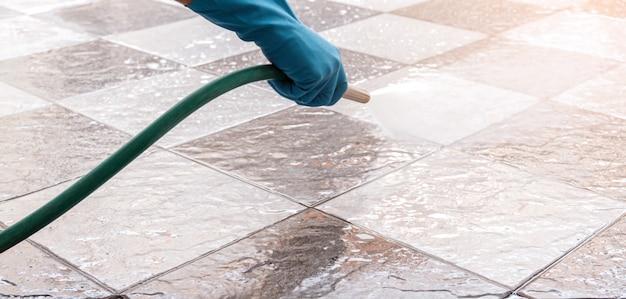 Hand van de mens die blauwe rubberhandschoenen draagt die een slang gebruiken om de tegelvloer schoon te maken. Premium Foto