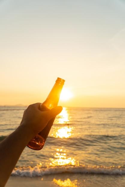 Hand van de mens houdt bierfles en houdt zijn hand in de lucht in de avond met zonsondergang. Premium Foto