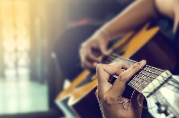 Hand van de mens in klassieke gitaar Premium Foto