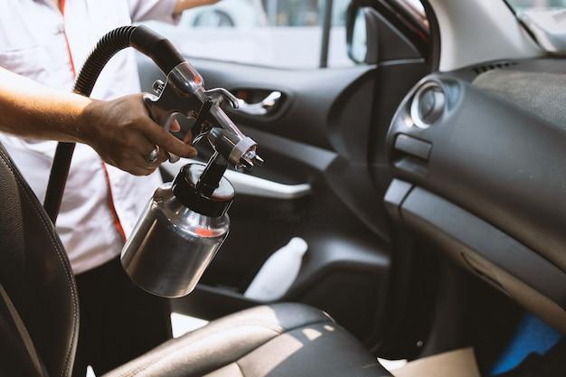 Hand van de mens spuit het covid-19-virus in de auto met soft-focus en over licht in de muur Premium Foto