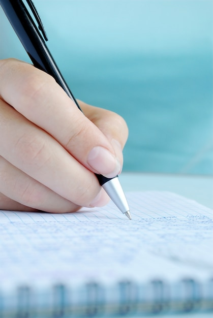 Hand van de vrouw het schrijven van vermeldingen in een notitieblok Premium Foto