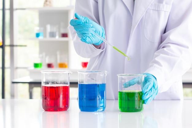 Hand van de wetenschapper met het bedrijf injectie laboratorium chemische test in het laboratorium. wetenschap. Premium Foto