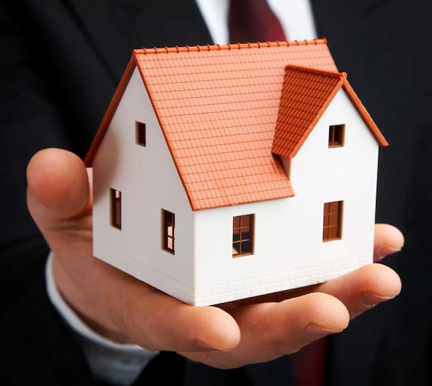 Hand van de zakenman met het huis. Premium Foto