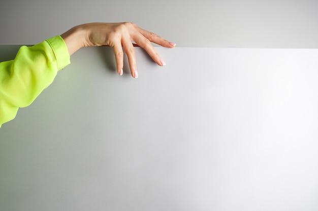 Hand van een jonge vrouw in een lichte blouse op een grijze achtergrond met plaats voor tekst, close-up. mooie franse manicure. spa en manicure concept. Premium Foto