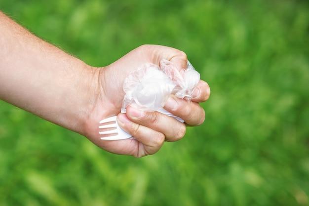 Hand van een klein meisje met plastic afval op groen gras in het park Premium Foto