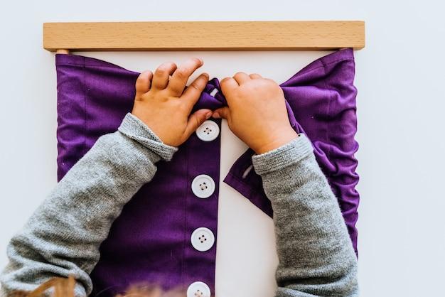 Hand van een student die montessorimateriaal in een klaslokaal behandelt. Premium Foto