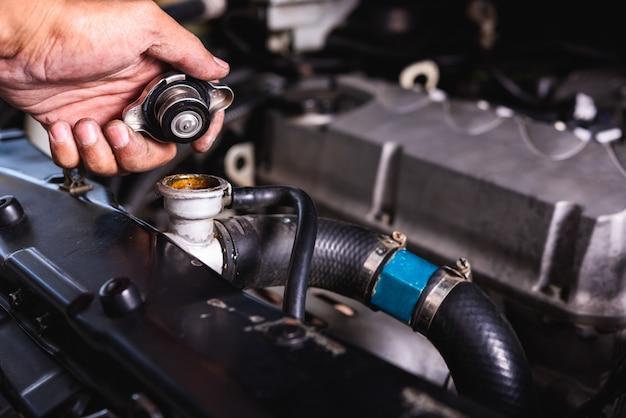Hand van het auto mechanische de controlekoelwater van de technicusdienst Premium Foto
