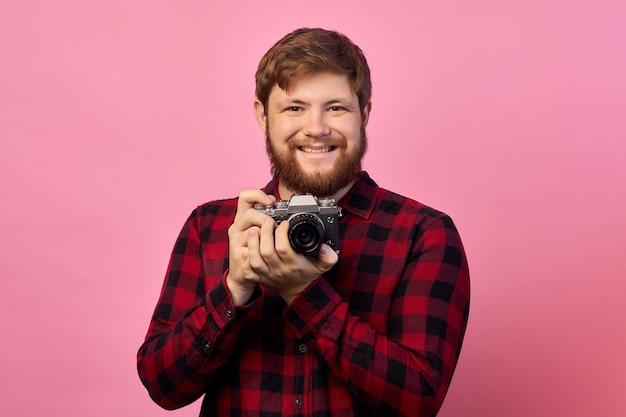 Hand van jonge spaanse man met vintage camera over geïsoleerde roze achtergrond Premium Foto