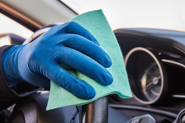 Hand van man in blauwe beschermende handschoen veegt stuurwiel met een doek af. desinfectie tijdens coronavirus- of covid-19-bescherming. Premium Foto