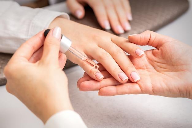 Hand van manicure giet olie door pipet op nagelriem van nagels van jonge vrouw in de schoonheidssalon Premium Foto