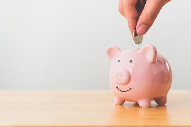 Hand van mannelijke of vrouwelijke munten in piggy bank zetten Premium Foto