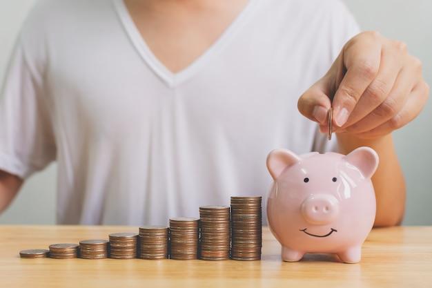 Hand van mannetje die muntstukken in spaarvarken met van de de stap groeiend groei van de geldstapel de besparingsgeld zetten Premium Foto