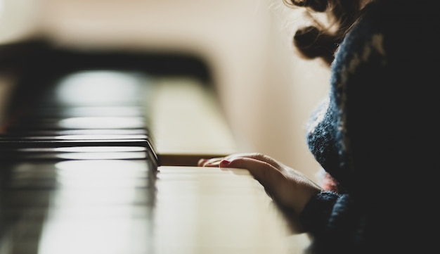 Hand van meisjepeuter die de piano speelt. Premium Foto