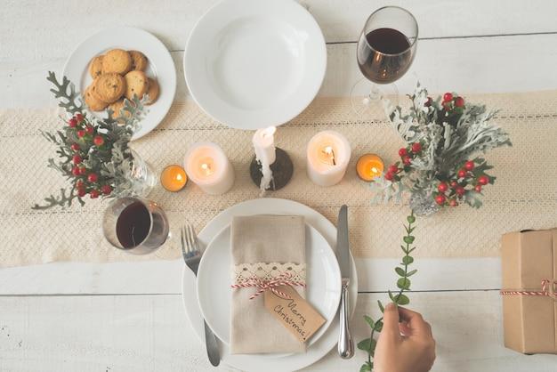 Hand van onherkenbare vrouw die groene tak op de tafel van het kerstmisdiner zet Gratis Foto