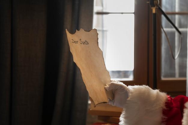 Hand van santa met een aan hem geadresseerde brief Gratis Foto