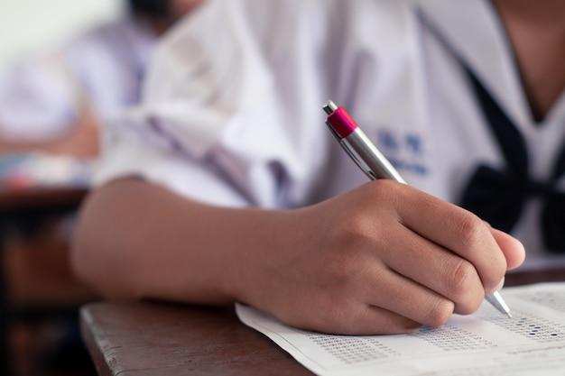 Hand van studenten schrijven en examen afleggen met stress in de klas Premium Foto