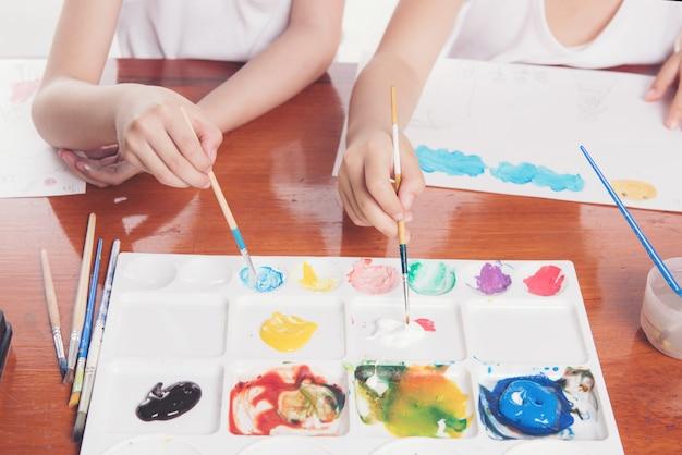 Hand van twee schoolmeisjes gebruik penseel onderwijs concept Premium Foto