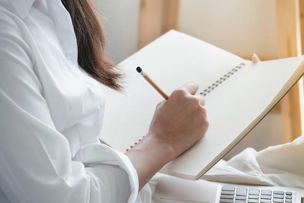 Hand van vrouw in vrijetijdskleding die potlood houden die leeg notitieboekje schrijven. Premium Foto