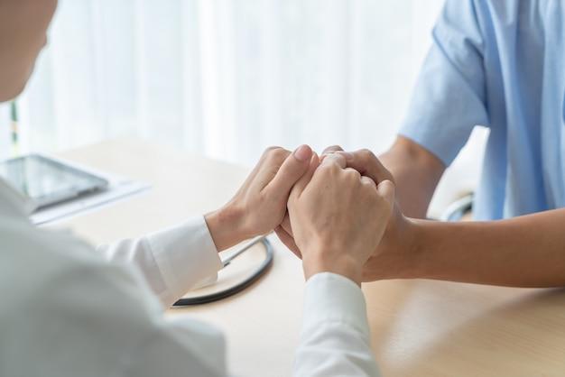 Hand van vrouwelijke artsenholding op haar hogere patiënt Premium Foto