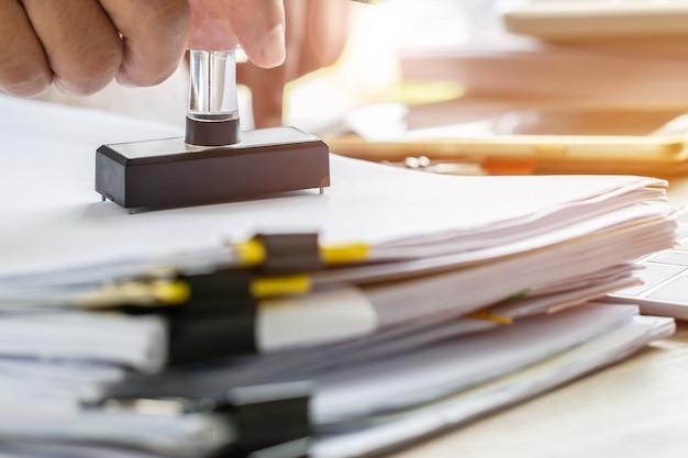 Hand van zakelijke persoon stempelen op goedgekeurde aanvraagformulier of notaris openbare stempeldocumenten Premium Foto