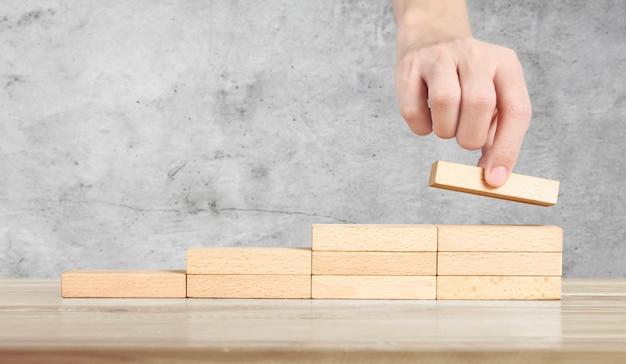 Hand vergelijken persoon opvoeren houtblok stapelen als stap trap Premium Foto