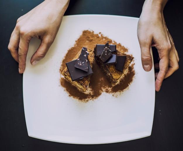 Hand versierd met mooie chocolade cake van vrouwen close-up op tafel Premium Foto
