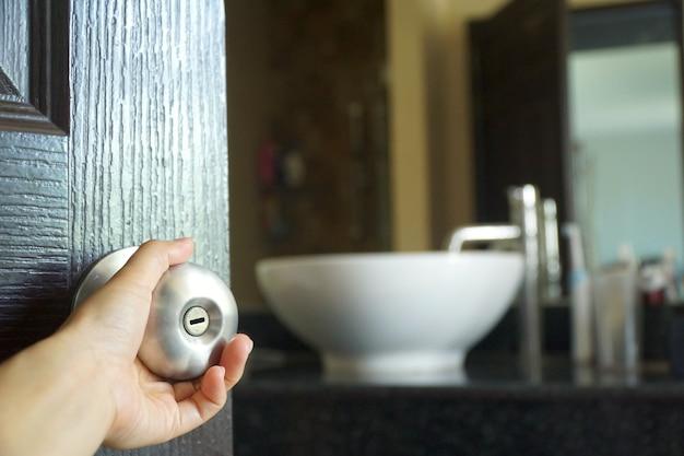 Hand vrouw met deurklink om de badkamer in haar huis te openen ...