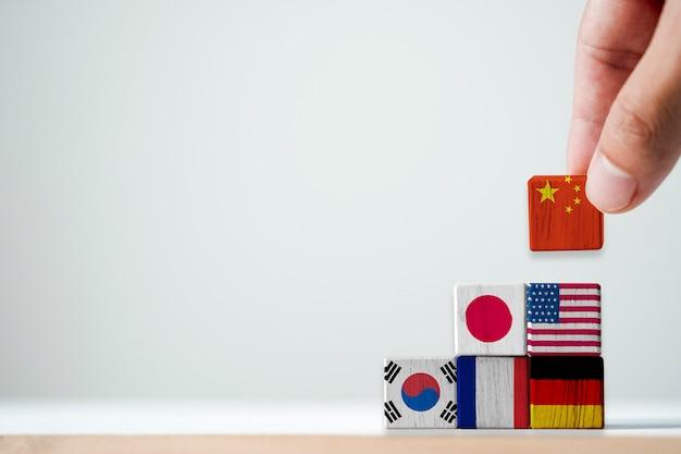 Hand zetten drukscherm china vlag op de top van de internationale vlag. het is meer een symbool van economische groei in china dan andere landen in de wereld. - economisch concept. Premium Foto