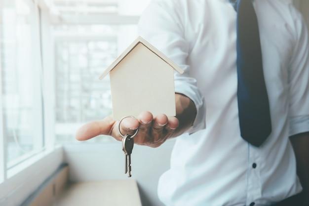 Handagent met huis in palm en sleutel op vinger. Gratis Foto