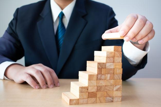 Handbediende houten blokken zakenlieden op elkaar gestapeld om een trap te ontwikkelen Premium Foto