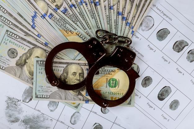 Handboeien op honderd dollar amerikaanse bankbiljetten de corruptie in de criminele vingerafdrukkenkaart Premium Foto
