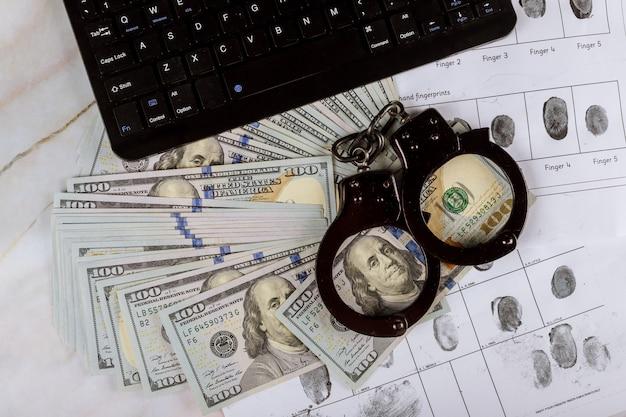 Handboeien op honderd dollarbiljetten met computertoetsenbordtechnologie van vingerafdruk Premium Foto