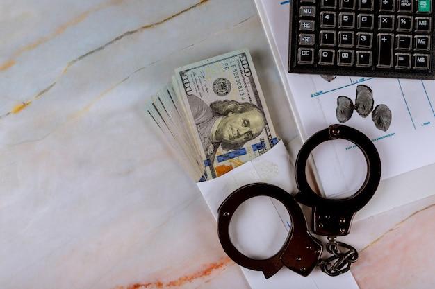 Handboeien van amerikaanse dollars bankbiljettencalculator van het vingerafdrukkengeld Premium Foto