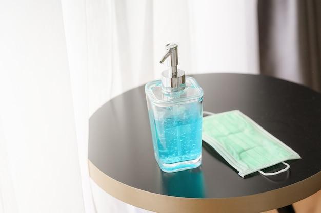 Handdesinfecterend alcohol gel fles voor handhygiëne en medische chirurgische maskers op tafel in huis Premium Foto