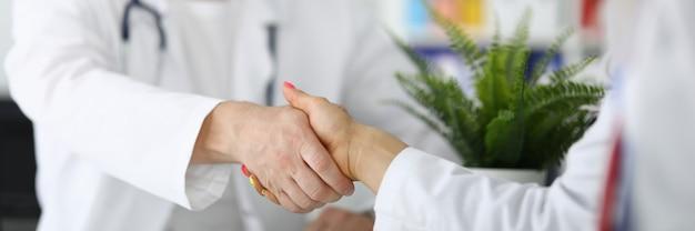 Handdruk tussen twee artsen in witte jassen. medisch succesvol arrangement concept Premium Foto