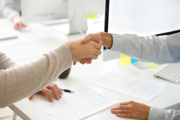 Handdruk van man en vrouw na het ondertekenen van bedrijfscontract, close-up Gratis Foto