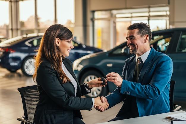 Handelaar die sleutel geeft aan nieuwe eigenaar en handen schudt in autoshow of salon. Premium Foto