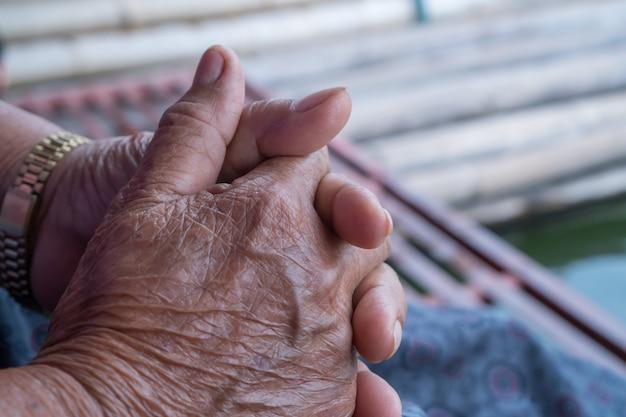 Handen aziatische oudere vrouw grijpt haar hand op schoot Premium Foto