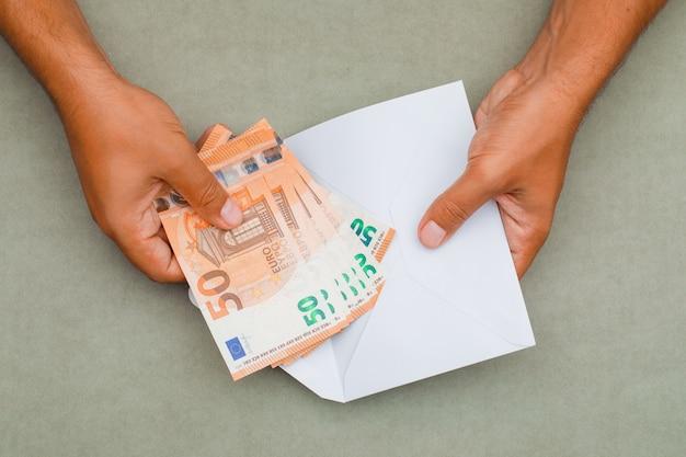 Handen bankbiljetten aanbrengend envelop. Gratis Foto