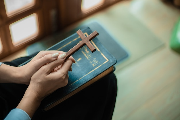 Handen bidden met bijbel en houten kruis. Premium Foto