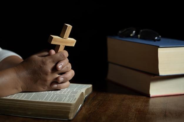 Handen bidden tot god terwijl ze het kruissymbool vasthouden. Gratis Foto